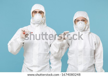 People in protective suit respirator mask hold blood test result Sample tube isolated on blue background studio. Epidemic rapidly spreading coronavirus 2019-ncov originating in Wuhan virus concept
