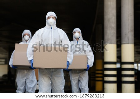 People in protective suits and masks delivering vaccine of coronavirus to population