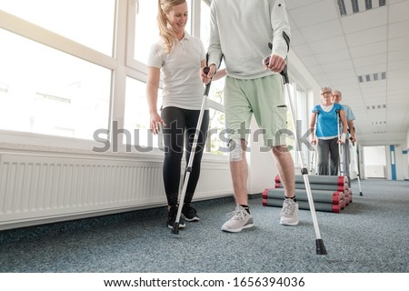 People in rehabilitation learning how to walk with crutches after having had an injury Stock photo ©