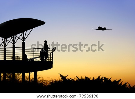 People in silhouette watching an airplane take off