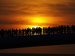 People in sunset time on the bridge