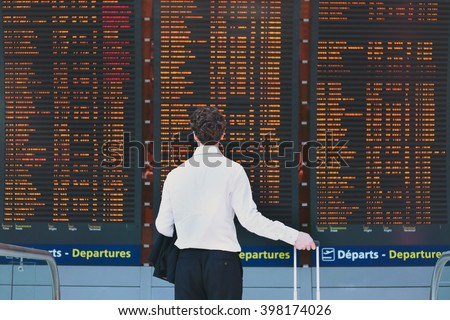 people in the airport, business travel, passenger looking at timetable screen board