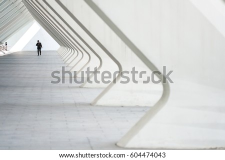 People in the architectural perspective. The sloping lines of the architecture. The man in the suit comes in a bright corridor in a modern building #604474043