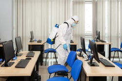 People in virus protective suits and mask disinfecting buildings of corona virus with the sprayer