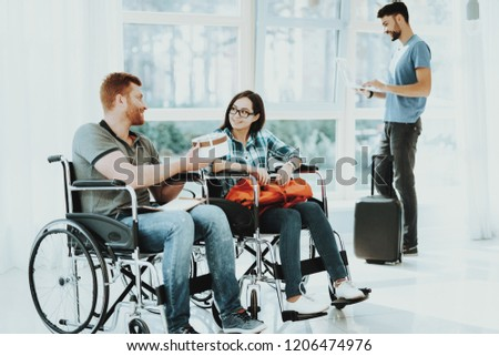 People in Wheelchair. Airport Hall. Woman in Wheelchair. Room Panoramic View. Smiling Woman Disabled. Romantic Meeting Disabled. People with Limited Opportunities. Gives Gift. Gives Teddy Bear.