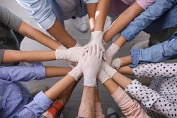 People in white medical gloves stacking hands indoors, top view