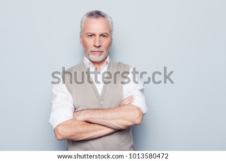 People individual lifestyle concept. Portrait of virile serious minded self-assured pensive granddad with crossed hands beige knitted waistcoat isolated on gray background copy-space