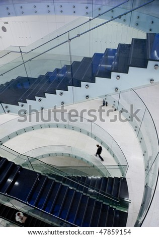 people inside a modern building (color toned image; motion blurred image)