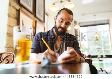 people, inspiration, freelance and leisure concept - man with beer writing to notebook at bar or pub
