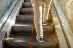 People is going up by escalator in any building with flare or light from the side and shadow on steps in the morning or afternoon.