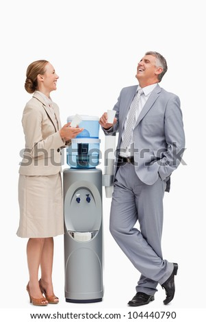 People laughing next to the water dispenser against white background - stock photo