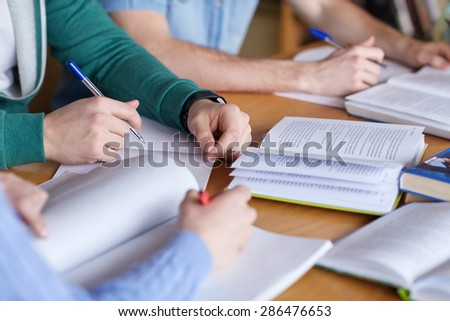 people, learning, education and school concept - close up of students hands with books or textbooks writing to notebooks