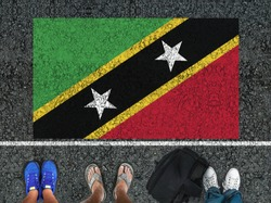 people legs are standing on asphalt road next to flag of Saint Kitts and Nevis and border