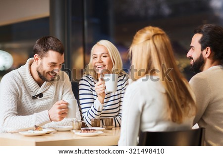 people, leisure and communication concept - happy friends meeting and drinking tea or coffee at cafe #321498410