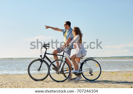 people, leisure and lifestyle concept - happy young couple riding bicycles on beach #707246104