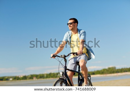 people, leisure and lifestyle concept - happy young man riding bicycle along summer beach #741688009