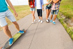 people, leisure and sport concept - close up of teenage friends with longboards and drinks outdoors