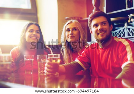 people, leisure and sport concept - happy friends or football fans drinking beer and watching soccer game or match at bar or pub #694497184
