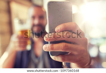 Photo of people, leisure and technology concept - close up of man with smartphone drinking beer and taking selfie at bar or pub