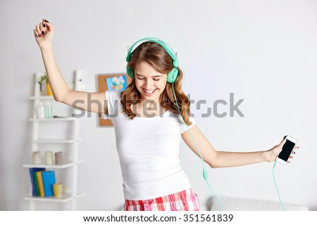 people, leisure and technology concept - happy woman or teenage girl in headphones listening to music from smartphone and dancing on bed at home #351561839