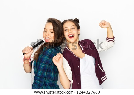 people, leisure and technology concept - smiling teenage girls in earphones listening to music and singing to hairbrush and having fun over white background