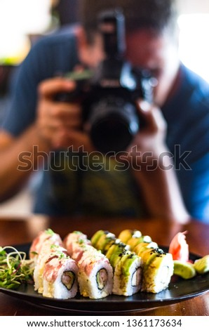 People, leisure, food, food and technology - close up of man with camera taking a picture of sushi in the restaurant.