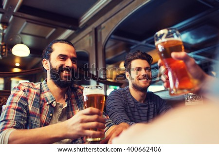 people, leisure, friendship and and bachelor party concept - happy male friends drinking beer at bar or pub
