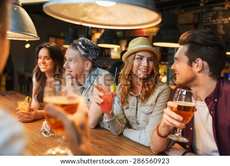 people, leisure, friendship and communication concept - group of happy smiling friends drinking beer and cocktails talking at bar or pub #286560923