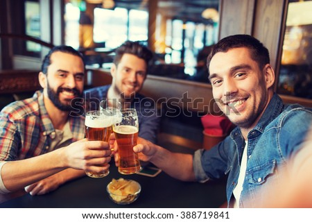 people, leisure, friendship, technology and bachelor party concept - happy male friends taking selfie and drinking beer at bar or pub