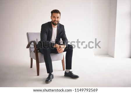 People, lifestyle, business, style, fashion and men's wear concept. Positive successful young CEO sitting in armchair, smiling at camera, dressed in elegant shoes, trousers, jacket and white t-shirt