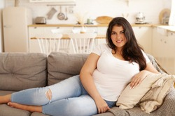 People, lifestyle, rest and relaxation concept. Attractive happy young Latin woman in casual clothes relaxing indoors after hard working day, stretching bare feet on sofa, smiling, being in good mood
