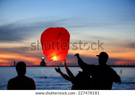 People lighting Paper lantern. Motion blur on lantern, main focus on Man in hat.