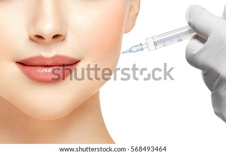 People, Lips, cosmetology, plastic surgery and beauty concept - beautiful young woman face and hand in glove with syringe making injection