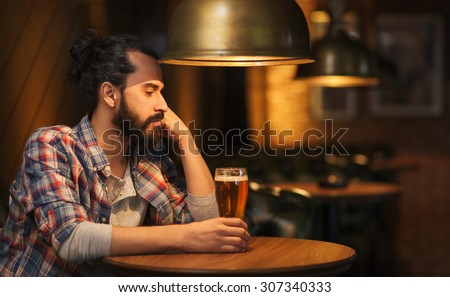 people, loneliness, alcohol and lifestyle concept - unhappy single man with beard drinking beer at bar or pub