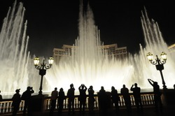 People look at night view of the fountain of Bellagio, Las Vegas, Nevada, USA