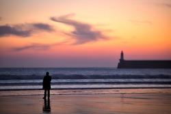 people looking at a vivid sunsetat les sables d'olonne beach