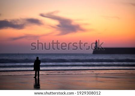 people looking at a vivid sunsetat les sables d'olonne beach Stock fotó ©