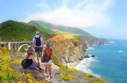 People looking at beautiful summer mountains landscape.Family on hiking trip, Bixby Bridge,  famous bridge on highway 1 in California over Pacific Ocean. Big Sur, California, USA