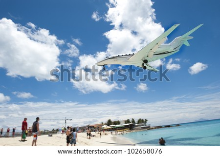People looking on as a big airplane flies over the beach.