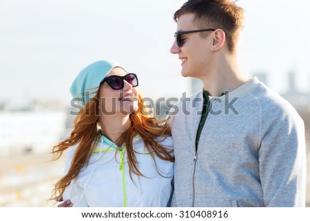 people, love and friendship concept - happy teenage couple walking in city