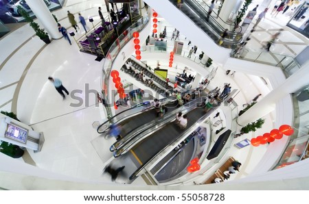 People make shopping in big modern mall. Crowd in motion blur