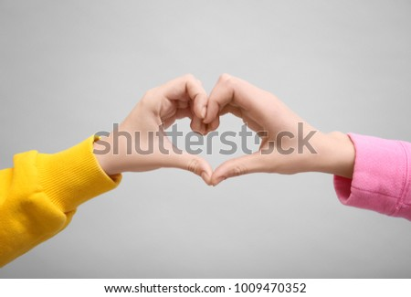 People making heart symbol with their hands on light background #1009470352