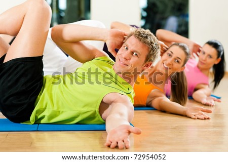 People, man and women, exercising doing sit-ups in gym or fitness club