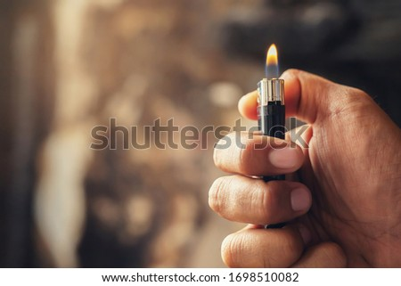 people man hand holding burning gas lighters arson conflagration damage background. Portable device used to create a flame. Safety and Set fire to insurance concept.  Stock photo ©