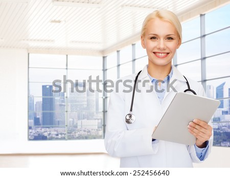 people, medicine and profession concept - smiling young female doctor with tablet pc computer and stethoscope over clinic background