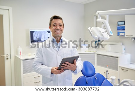 people, medicine, stomatology and healthcare concept - happy middle aged male dentist in white coat with tablet pc computer at dental clinic office