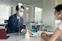People meeting across an acrylic partitions. Infection prevention.