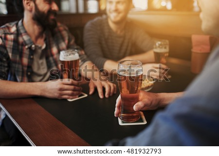 people, men, leisure, friendship and communication concept - close up of happy male friends drinking draft beer at bar or pub