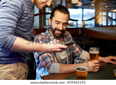 people, men, leisure, friendship and communication concept - happy male friends with smartphones drinking draft beer at bar or pub #459462193