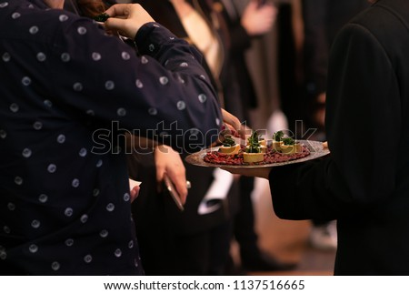 People mingle with canapes